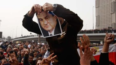 An anti-government protester tears up a picture of Egyptian President Hosni Mubarak.