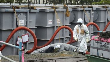 Ongoing disaster: workers at the crippled Fukushima Daiichi nuclear power plant, where contaminated water is now washing into the sea.