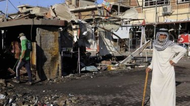 Iraqi civilians gather the morning after a car bombing in Baghdad, Iraq, on October 9, 2014.