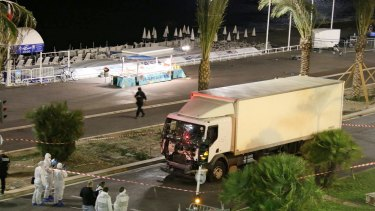 Authorities investigate a truck after it ploughed through Bastille Day revellers in the French resort city of Nice last July.