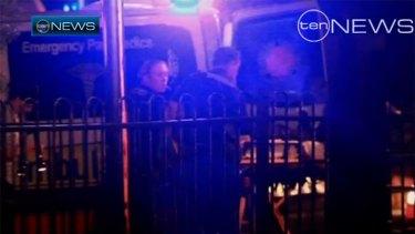 Paramedics treat Senior Constable Leeding after last night's shooting.
