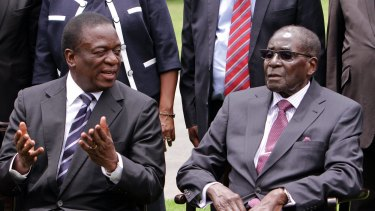 Emmerson Mnangagwa, left, then Vice President of Zimbabwe chats with Zimbabwean President Robert Mugabe after the swearing in ceremony at State House in Harare.