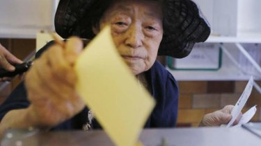 A woman casts her ballot at a polling station during the upper house election in Tokyo.