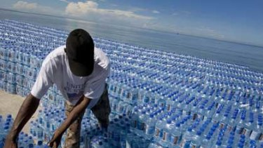A Haitian man unloads water donated by the World Food Program after Tropical Storm Hanna passed through the region, dumping heavy rains that flooded region and claimed at least 136 dead.
