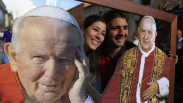 Two of the faithful pose with pictures of Pope John Paul II (L) and Pope John XXIII in front of St Peter's Square, in Rome ahead of their canonisation on Sunday.
