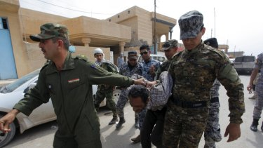 Iraqi security forces arrest a member of the Islamic State in Tikrit on Wednesday.