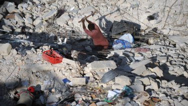 Will take years to rebuild ... Haitian men search through the rubble of a destroyed home in Port-au-Prince.