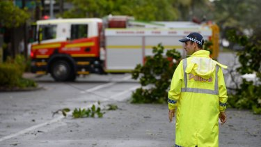 A policeman stands guard to keep onlookers away from fallen powerlines laying across a street at Port Douglas.