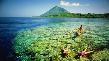A man in a traditional canoe watches two two snorkellers in Manado.