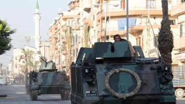 Civil war imminent ... armored vehicles patrol the empty streets of the Sunni Muslim Bab al-Tebbaneh neighbourhood in Tripoli after ten people were killed.