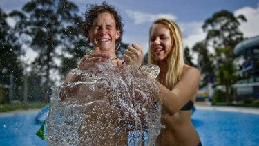 Canberra High year 10 students Jeremy Bradbury and Triska Hoelzl escape the heat at the Big Splash water park with water filled balloons.