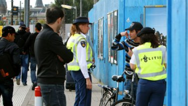 Tension ... police check identity papers in Amsterdam.