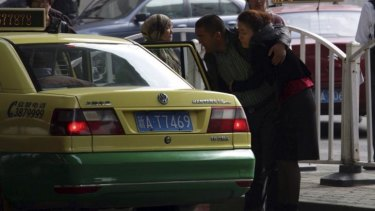 Ilham Tohti's wife Guzaili Nu'er is helped into a taxi after the verdict.