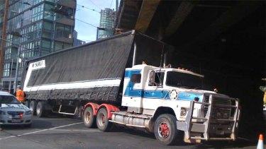 The semi-trailer stuck under the bridge.