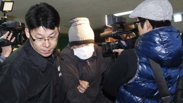 Arrested … a Chinese fisherman is led away by police.
