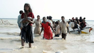 Fears asylum seekers could face torture: Photograph from May 15, 2009 shows Tamil civilians wading and using boats to escape the island's war zone.