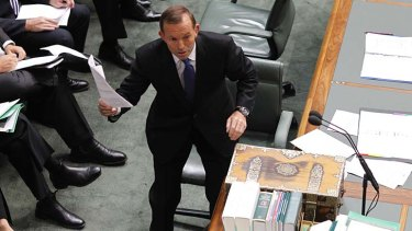 Leader of the Opposition Tony Abbott tables the power bill during Question Time.