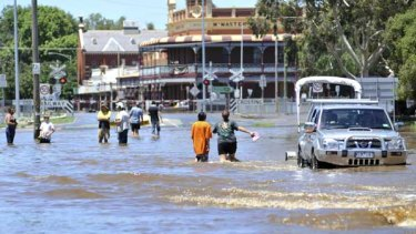 Residents wade through the main street of Rochester as the Campaspe River reached a record 9.15 metres yesterday afternoon, inundating 80 per cent of the town.