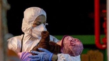 A rescuer cradles a child in  Pozzallo.