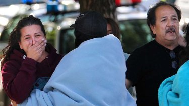 Jessica Reyes, Jason Valdez's sister, and his father, Duane Valdez, react after hearing a loud explosion as SWAT teams storm the room Jason was holding his hostage in.