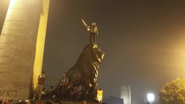 An anti-Mursi protester wearing a Guy Fawkes mask celebrates on top of a lion statue near Tahrir square.