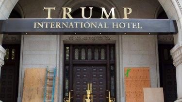 Plywood covers up anti-Trump graffiti at the entrance to his new Washington hotel.