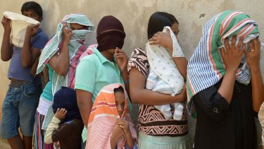Sri Lankan asylum seekers sent back by Australia queue to enter the magistrate's court in the southern port district of Galle, Sri Lanka, in July.