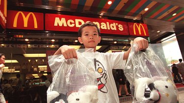 A boy displays giveaway Hello Kitty dolls used in a McDonald's promotion in Hong Kong.