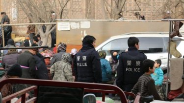 Watchful eye: Police wait outside Hotan Mosque during Friday prayer.