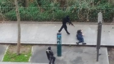 A hooded gunmen stands over a wounded police officer before executing him at point-blank range in this still from an amateur video capturing the terrorist attack.