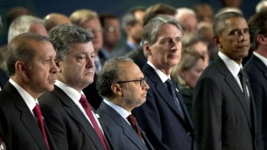 Leaders stand for a moment of silence for NATO members killed in Afghanistan.