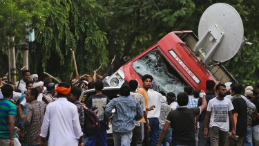 Dera Sacha Sauda sect members overturned a OB van on the streets of Panchkula, India on Friday.
