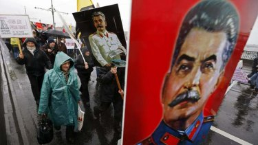 """People carry posters of late Soviet leader Joseph Stalin as they attend a """"Patriotic March"""" demonstration, organized by the Rodina (Motherland) political party, on National Unity Day in St. Petersburg."""