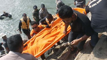 Tragedy: Rescuers carry the body of a victim killed after a boat carrying asylum seekers sank off Java island.