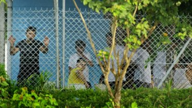 Asylum seekers sit behind the wire of the Manus Island detention centre.