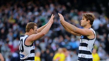 High fives: Steve Johnson (left) celebrates a goal he kicked after receiving a cheeky handball from Tom Hawkins.