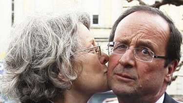 Front runner ... Francois Hollande, right, is kissed by a supporter in Tulle. The Socialist challenger was expected to defeat Nicolas Sarkozy in the first round of voting.