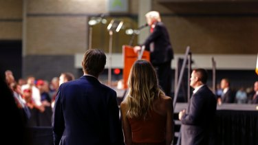 Eric Trump, foreground, son of Republican presidential candidate Donald Trump, listens as his father delivers a campaign speech in Charlotte, North Carolina.