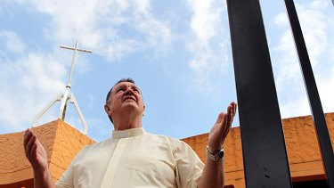 No way in ... Monsignor Brian Rayner outside the church from which he banned the Greens.