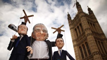 A man in a Rupert Murdoch mask holds puppets depicting British Prime Minister David Cameron (left) and Culture Secretary Jeremy Hunt outside Parliament.