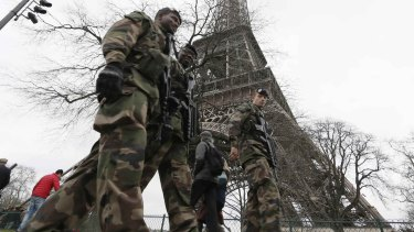 French soldiers patrol near the Eiffel Tower in Paris.