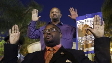Reverend K.W. Tulloss and community activist Najee Ali hold up their arms during a demonstration in Los Angeles following the grand jury decision in the shooting of Michael Brown.