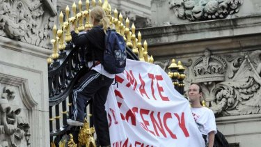 Protesters from the Climate Siren group hang a banner from the gates of Buckingham Palace.