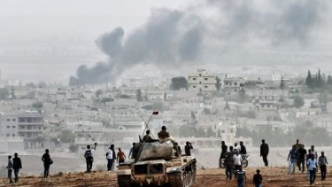 Turkish soldiers on a tank and Kurdish people look at the Syrian town of Kobane.