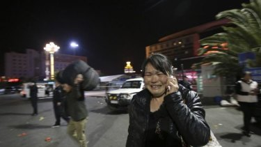 A woman reacts, at the crime scene outside a railway station after an attack, in Kunming, in southwestern China's Yunnan province.