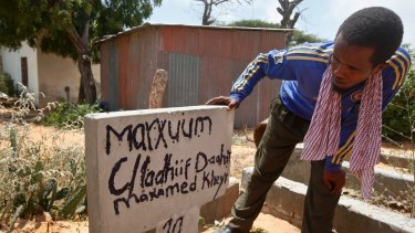 A Somali man looking for news of his missing brother looks at grave boards at a cemetery in Mogadishu on Tuesday.