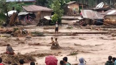 Villagers carry cross raging flood waters in Lanao del Norte, Zamboanga Peninsula, southern Philippines.