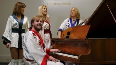 Cast members of the ABBA-inspired musical <i>Bjorn Again</i> play the Georg Bolin grand piano at Sotheby's auction house in London.