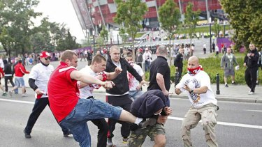 Kick to the head ... fans brawl outside the stadium.