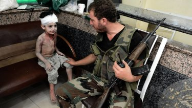 Victims rising … a Free Syrian Army fighter comforts a boy who was wounded when a shell hit his home in Aleppo.